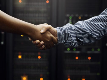 Why You Need a Turnkey Data Center Partner   Image of two arms shaking hands in front of server racks